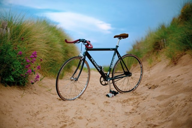 bicicleta aparcada en la arena para hablar del síndrome del ciclista o atrapamiento del nervio pudendo