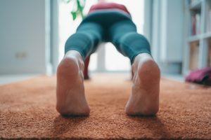 Deportista tumbado en el suelo haciendo ejercicios de rehabilitación para el tendón de Aquiles